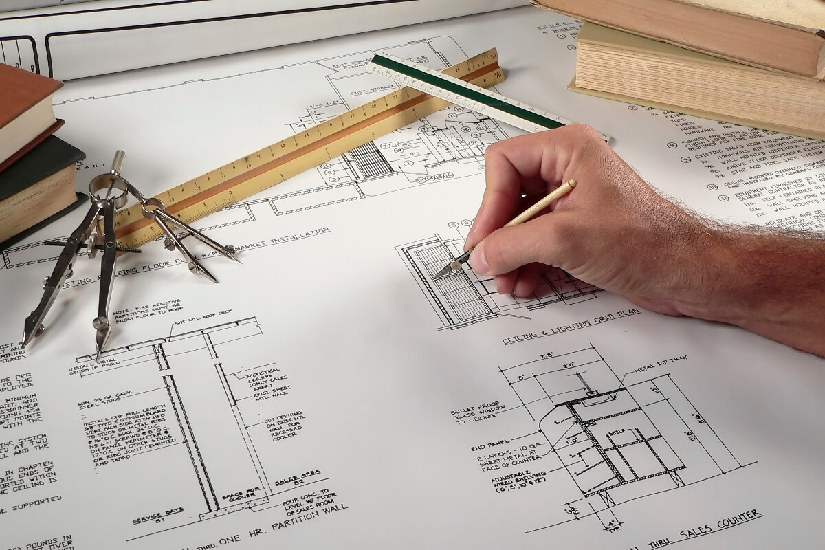 Hand Drawing Floor Plans with Compasses and Rulers on Table