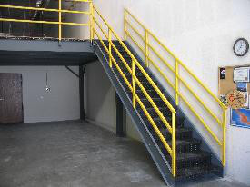 Metal stairs with yellow railing, in a warehouse